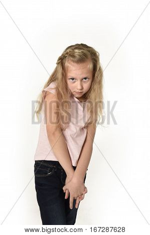 young sweet little child girl with beautiful blonde hair in casual clothes looking shy and timid as if scared or overwhelmed isolated on white background
