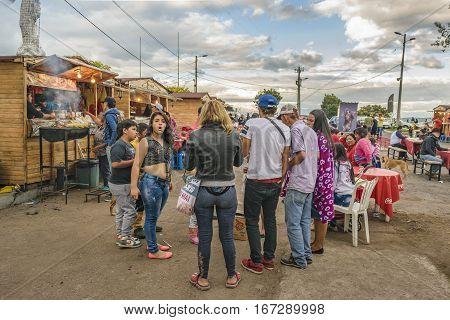 QUITO ECUADOR FEBRUARY - 2016 - People at ecuadorian food street market stands located in the famous panecillo landmark in Quito Ecuador.