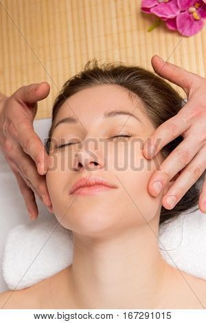 A Young Woman's Face, With Taut Skin And Hands Of The Masseur