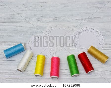 Bobbins with colorful threads on old wooden table background Sewing background with copy space
