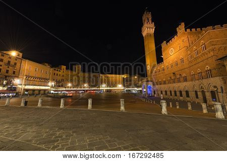 Piazza del Campo (Campo square) by night with the tower del Mangia (Tower of Mangia) and the Town Hall in the downtown of Siena Toscana (Tuscany) Italy