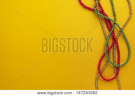 Multi color Mardi Gras beads on paper background.