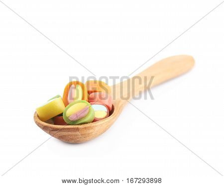 Spoon full of licorice candies isolated over the white background