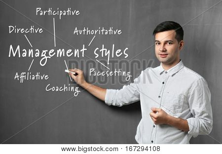 Management styles concept. Young man with piece of chalk on gray background