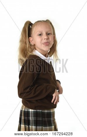little sweet schoolgirl with pigtails playful and naughty taking tongue out mocking playful wearing school uniform isolated on white background