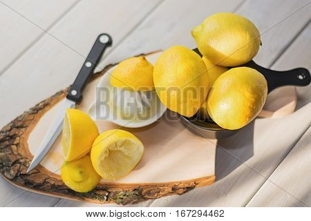 Juicer for lemon on a wooden plank and cut and whole lemons around.
