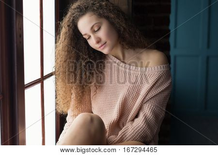 Pretty girl with long curling hair sitting on a windowsill.