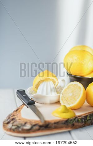 Cut lemon with knive on a wooden board.