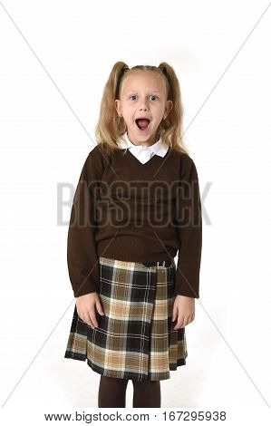 young beautiful and sweet schoolgirl in pigtails and school uniform looking amazed shocked and surprised in female child face expression isolated on white background