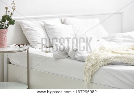 Bedroom interior with bed and flowers on nightstand