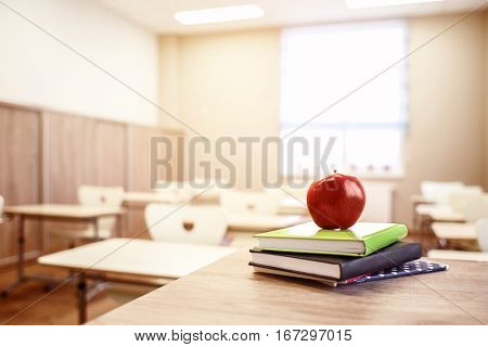 School teacher's desk with stack of books and apple