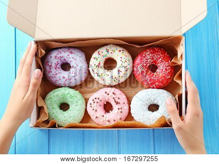 Female hands holding box with colorful donuts on blue wooden background