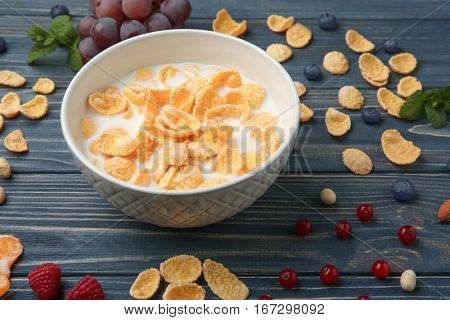 Tasty cornflakes with milk on gray background