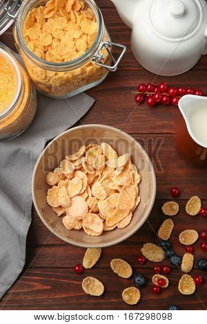 Tasty cornflakes with blueberries and redcurrant on wooden background