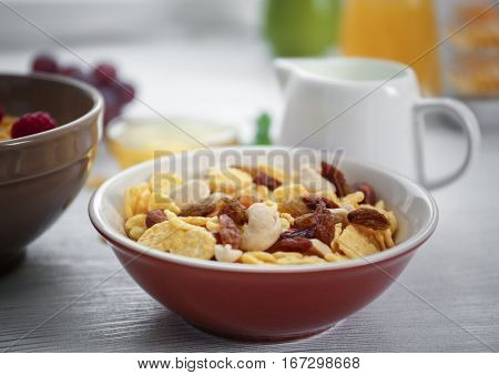 Tasty cornflakes with raisins and nuts and honey on table