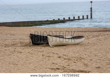 Two rowing boats on the beach. Shows a beach and the sea with groyne and two small rowing boats which have been pulled up onto the sand and chained to keep secure.