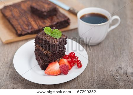 Healthy gluten free brownies made with sweet potato and coconut flour. Paleo style brownies on a wooden table selective focus