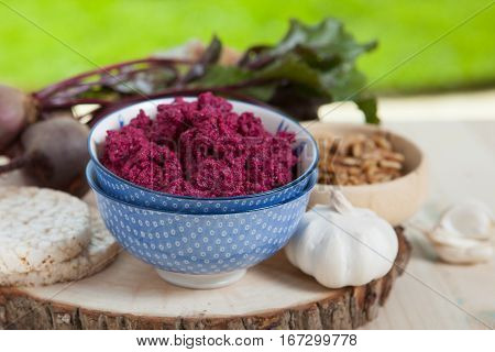 Beetroot pesto in a blue bowl on a wooden table with garlic beetroot and rice cakes on the back selective focus