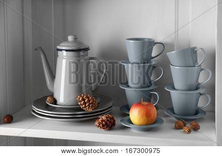 Tea set in wooden cupboard