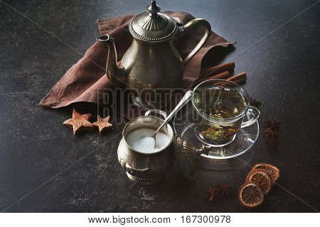 Fresh tea in cup and vintage  dishware on kitchen table
