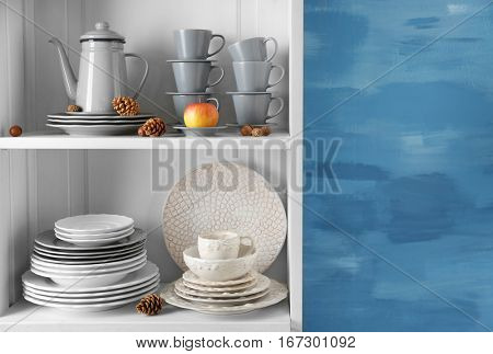 Different clean dishes in cupboard in the kitchen
