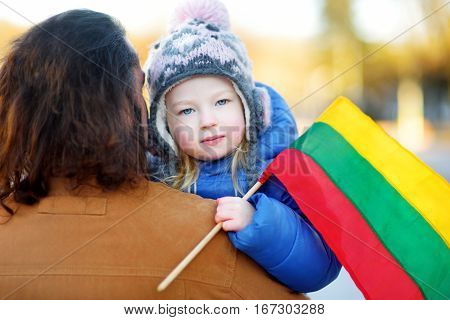 Father and daughter with a flag on Lithuanian independence day holding tricolor Lithuanian flag in Vilnius