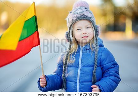 Cute little girl celebrating Lithuanian Independence Day holding tricolor Lithuanian flags in Vilnius