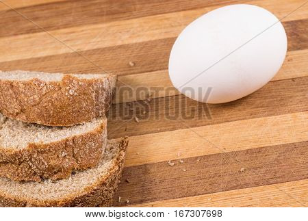black bread and a chicken egg on a wooden background is useful products for a healthy diet
