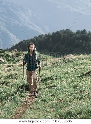 Hiker young woman with trekking poles walking on path in summer mountains