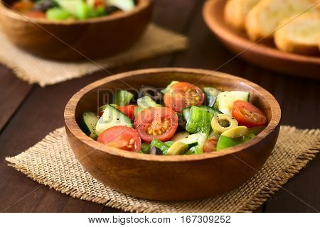 Fresh salad of black and green olives cherry tomatoes green bell pepper and cucumber seasoned with salt pepper dried oregano and basil served in wooden bowls photographed on dark wood with natural light (Selective Focus Focus in the middle of the salad)