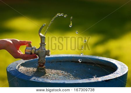 Water running in drinking fountain in park on summer day