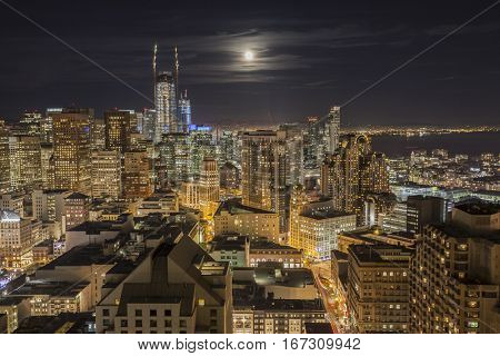 San Francisco, California, USA - January 13, 2017:  Downtown night view with moon rising over San Francisco Bay.