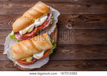 Appetizing bread with sausage and vegetables on wooden table