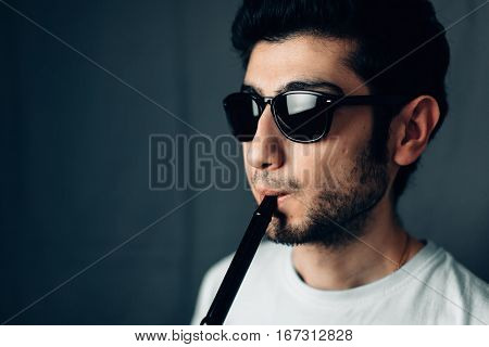 Young guy with glasses inhales through the mouthpiece of a hookah. Horizontal close-up portrait