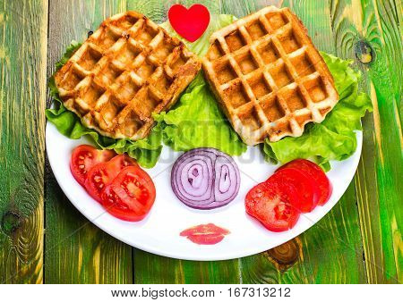 Liege waffles tomato onion and lettuce on a white plate. On wooden green background.
