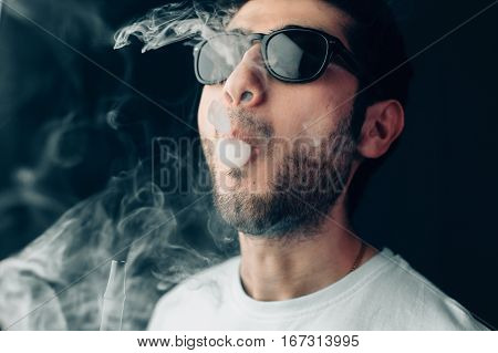 Young cool guy in sunglasses exhales a cloud of smoke. Studio horizontal portrait in close-up