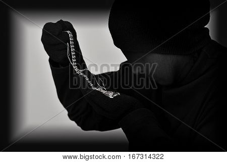 Female robber with black tights over her head holding and looking at the stolen jewellery. Black and white. Low key. Selective focus.
