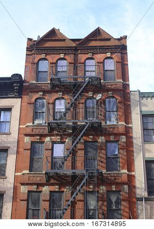 Brownstone building in New York City with fire escape staircase