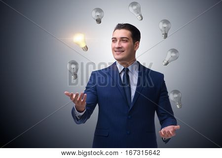 Businessman juggling lightbulbs in new idea concept