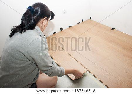 young beautiful woman puting laminate flooring closeup
