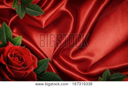 Red satin fabric draped in the form of heart and red rose for Valentine's day background