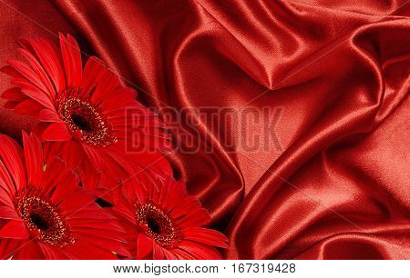 Red satin fabric draped in the form of heart and red gerbera flowers for Valentine's day background