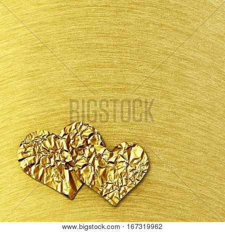 Two gold hearts on gold steel brushed background for Valentine's Day