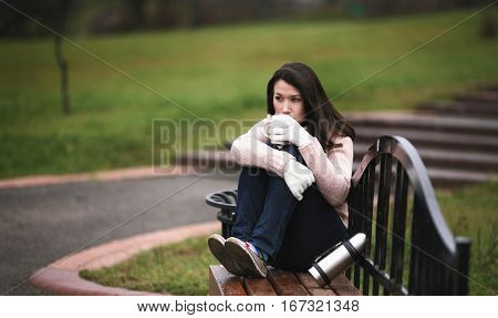 Beautiful brunette girl on bench in park. Lifestyle of young brunette woman drinking coffee in morning. Stunning girl in white gloves and warm pullover with cup of coffee outdoors. Brunette with natural makeup on soft green background.