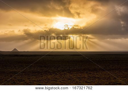 Colorful sunset over the vast landscape of Iceland with godbeams
