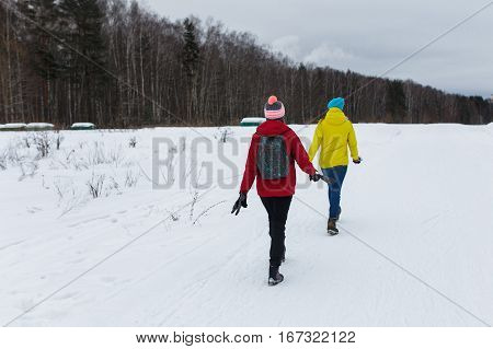 Young girlfriends go in winter woods in afternoon