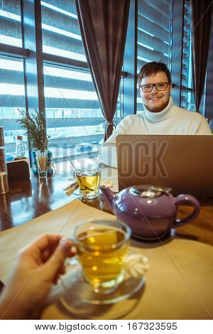 first-person view in cafe on working man with laptop