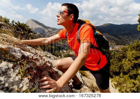Photo of young guy climbing on rock in mountains
