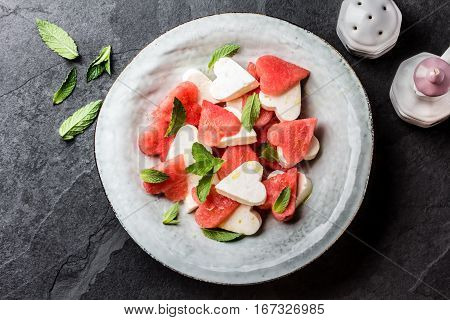 Mediterranean Italian Salad with watermelon and cheese feta cut as hearts and mint on grey plate on slate background. Valentine day menu consept. healthy food. Top view