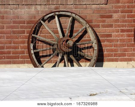 An abandoned wooden wheel with a steel rim leaning against  brick wall.